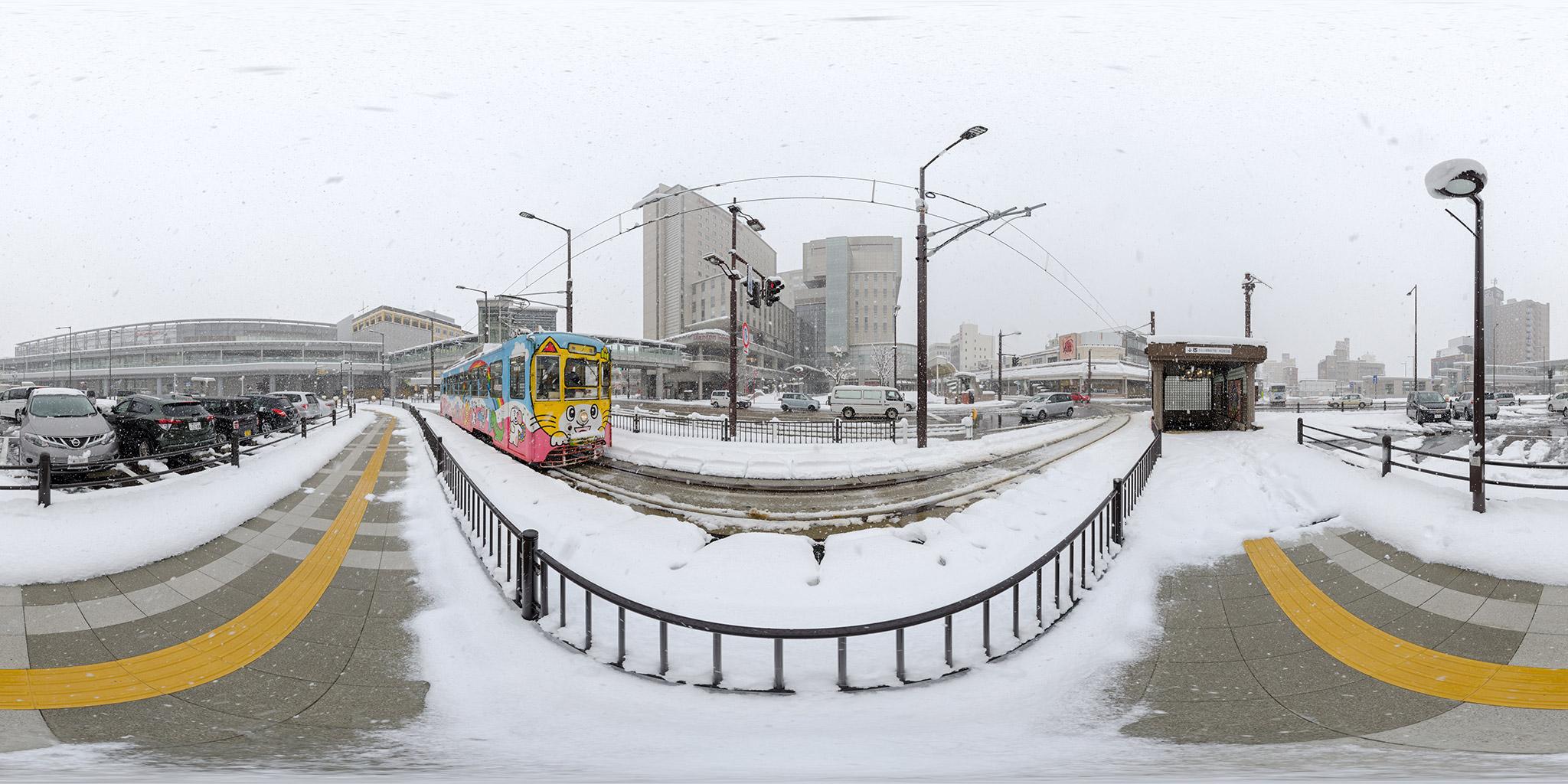 大雪の高岡駅前を行くデ7073